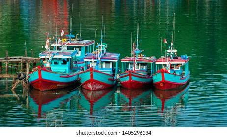 Beautiful scenery on early morning of colourful fishing boats park in a row with mirror reflections on the river water near Padang, West Sumatra Indonesia. (noise grain soft focus blurry visible)