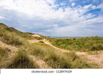 Beautiful scenery of Pembrokeshire coastline,South Wales, Uk in summer.Scenic landscape of british coast.Sand dunes covered with grass patches.Blue sky with clouds over horizon.Amazing places Uk.