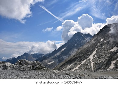 Beautiful scenery of Presena Glacier mountains against fluffy clouds around Passo del Tonale mountain pass in northern Italy between Lombardy and Trentino. Exploring high altitude hiking trail, summer