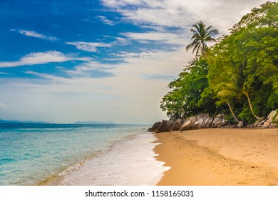 Beautiful scenery of the shoreline of Petani Beach on Perhentian Kecil Island in Malaysia. The secluded golden sand beach, the turquoise water, the blue sky and the trees makes this place a gem.