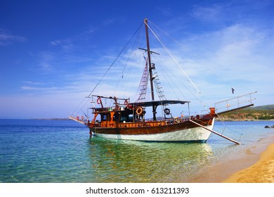 Beautiful scenery - traditional old fashioned cruise boat docked to the sand shore and colorful blue azure crystal clear water of Aegean Sea, Kassandra of Halkidiki peninsula, Greece, South Europe