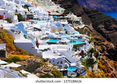 Beautiful scenery, traditional white cycladic architecture, chic hotels, azure pools, sunbeds and beach umbrellas surrounded with black volcanic rocks. Oia village, Santorini island, Cyclades, Greece