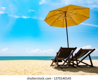 Beautiful scenery of two chairs and a white umbrella on the beach in summer. Copy area banner