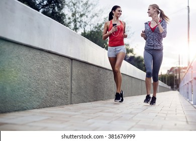 Beautiful scenery of two female joggers pursuing their activity outdoors in the city in dusk