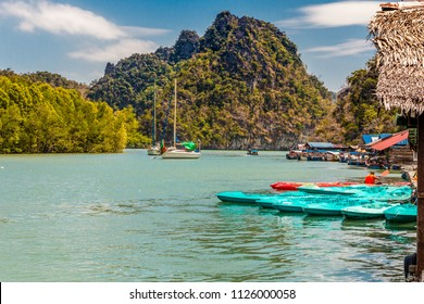 Beautiful scenery of two sailing boats next to a mangrove coastline and many moored kayaks and motorboats at a floating platform with a limestone formation in the background; in Kilim Geoforest Park.