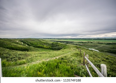 Beautiful scenery and views. Tall green grass fields, old wood fence, cloudy skies at Glenbow Ranch Provincial Park in Cochrane Alberta Canada