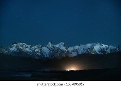 Beautiful scenery of white peaks mountains and glowing camp under night sky full of stars near Kel Suu Lake in Naryn region, Kyrgyzstan