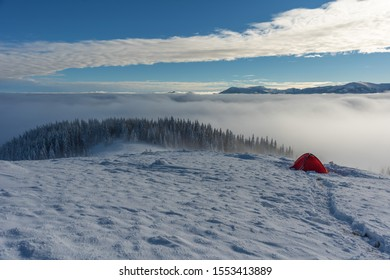 Beautiful scenery with winter snow-capped mountains, with fogs and contrasting snow structure and red tourist tent in the foreground, in locations in the Ukrainian Carpathians.