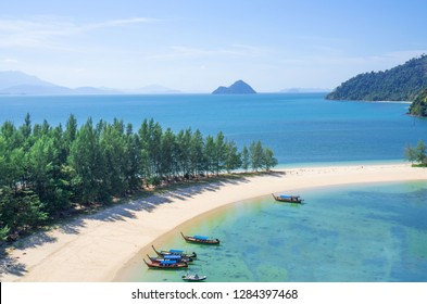 beautiful scenery with wood boat on the beach white sand in blue sea and blue sky on tropical beach .