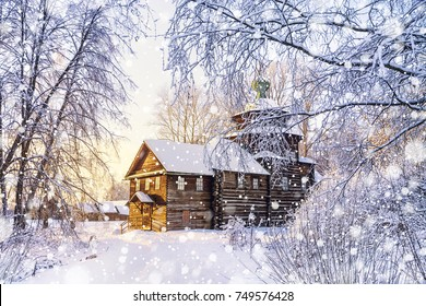 Beautiful scenery with a wooden church in a winter forest surrounded by frozen and covered snow trees in a frosty sunny day in Russia