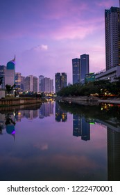 Beautiful scenes of reflected office buildings on the water with cloudy sky in the dusk, Jakarta, Indonesia