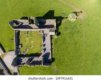 Beautiful scenic aerial birds eye view of old ruins of Clare Abbey in County Clare, Ireland. Irish rural countryside with old Irish religious Abbey in decay.