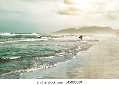 Beautiful scenic beach view at sunset with surfer siluette  on the ocean beach,  Florianopolis,  Brasil, South America