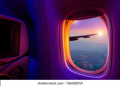 Beautiful scenic city view of sunset through the aircraft window. Image save-path for window of airplane.