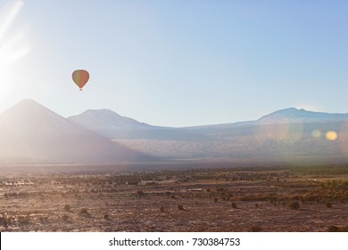 beautiful scenic landscape in atacama desert, chile with flying hot air balloon at sunrise with sun flare