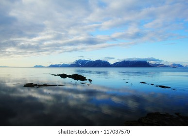 Beautiful scenic landscape - dramatic cloudy sky reflected at calm blue water against the background of distant rugged mountain range, Spitsbergen archipelago (Svalbard island, Norway), Greenland Sea