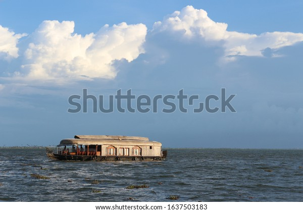 BEAUTIFUL SCENIC LANDSCAPE OF HOUSE BOAT ON THE CRYSTAL CLEAR BLUE WATERS OF LAKE VEMBNAD KERALA WITH A CLEAR BLUE BACKGROUND OF SKY WITH CLOUDS