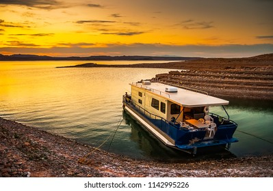 Beautiful and scenic landscape of the Lake Mead National Recreation Area with a houseboat moored to the shores of a bay with a dramatic sky at sunset, Nevada. Vacation and tourism concept.