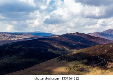 Beautiful scenic mountain landscape with clouds against the horizon, sun and shadow in Wicklow mountains Ireland.