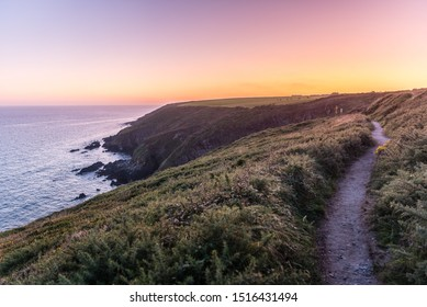 Beautiful scenic panorama sunset view of Ballycotton cliff walk, County Cork, Ireland, at dusk, calm sea, sun setting horizon, lonely path, popular hiking trail, twilight, ocean