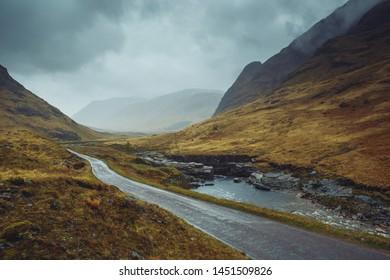 Beautiful scenic road in Glen Etive, Glen Coe Scotland. Landscape in rainy foggy weather.