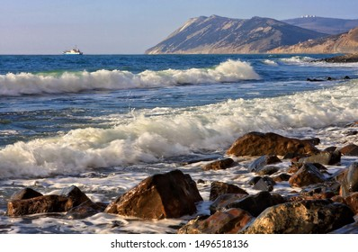 Beautiful scenic seascape of Black Sea by Bolshoy Utrish, Anapa, Russia with flock of sea gulls flying and waves breaking on sandy seashore. White seagulls on sunny beach under blue sky
