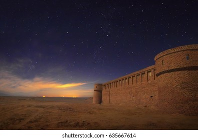 Beautiful scenic view - ancient iranian caravanserai (caravan serai) at the background of night sky full of stars and sunset in Maranjab desert near Kashan and Aran va Bidgol, Iran, Middle (Near) East