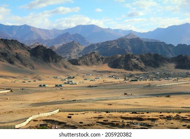 Beautiful scenic view - barren valley against the background of distant colorful mountain range and cloudy blue sky near Leh city, Ladakh, Himalaya, Jammu & Kashmir, Northern India, Central Asia