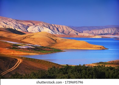 Beautiful scenic view, bright blue water of Al Wahda Dam Lake and barren mountain range settled by the last rays of declining sun at the background of evening sky, Taounate Province, Morocco, Africa