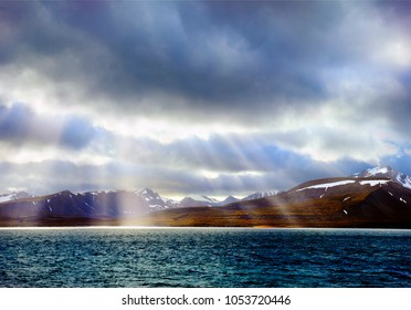 Beautiful scenic view, bright shafts struck through the cloud, black rocks and dark water of Istfjorden at the background of dramatic sky near Barentsburg, Norway, Spitsbergen island (Svalbard)