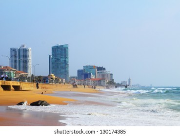Beautiful scenic view of city beach with a heavy surf and bright yellow sand against the background of modern skyscrapers and sea wall in Colombo - the capital of Sri Lanka island, Indian ocean