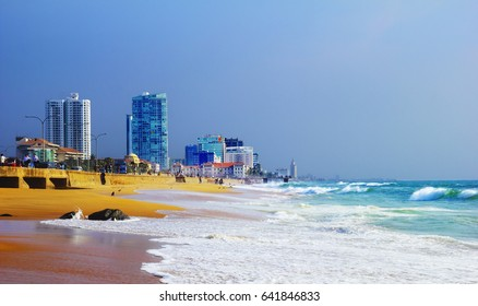 Beautiful scenic view of city beach with a heavy surf of Indian ocean and yellow sand at the background of modern skyscrapers, sea wall and blue sky in Colombo, the capital of Sri Lanka, South Asia