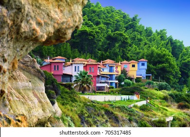 Beautiful scenic view, colorful hotel apartments, steep shore, bright wood foliage and blue sky near Fourka mountain, Kassandra of Chalkidiki (Halkidiki) peninsula, Greece, South Europe
