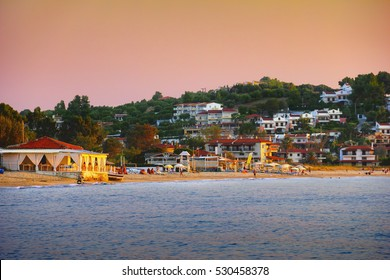 Beautiful scenic view - colorful pink sky at sunset above bright blue water of Aegean Sea, sand beach and houses, Fourka mountain, Kassandra of Chalkidiki (Halkidiki) peninsula, Greece, South Europe