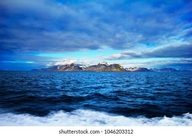 Beautiful scenic view, distant arctic land with rugged rocks covered with snow and moss at the background of dramatic blue sky in Bellsund, Spitsbergen (Svalbard island), Norway, Greenland Sea