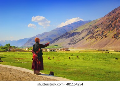 Beautiful scenic view: elder woman wearing traditional dress call sheep against the background of mountain range, colorful field and blue sky in Suru valley, Ladakh, Jammu & Kashmir, Northern India