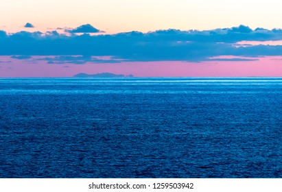 Beautiful scenic view of a Fata Morgana mirage on the sea and profile of Corsica island in the distance on the horizon at sunset, seen from the coast of Cinque Terre (Five Lands), Liguria, Italy