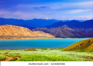 Beautiful scenic view, green field and colorful blue water of Toktogul lake under barren yellow and violet mountains at the background of dramatic cloudy sky, Tien Shan range, Kyrgyzstan, Central Asia