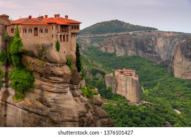Beautiful scenic view, Holy Orthodox Monastery of Rousanou (St. Barbara) and Varlaam, bright green foliage at the background of stone wall in Meteora, Pindos Mountains, Thessaly, Greece, Europe