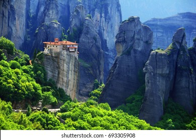 Beautiful scenic view, Holy Orthodox Monastery of Rousanou (St. Barbara) on the top of monolithic pillar, green foliage at the background of huge barren rocks in Meteora,  Thessaly, Greece, Europe