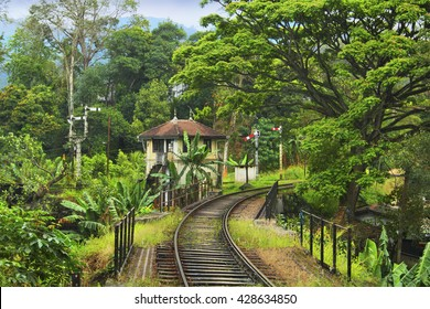 Beautiful scenic view: old historic english railway, bridge, the caretaker's house and bright tropical rain forest foliage - riding by train from Kandy to Badulla, Sri Lanka island, Southern Asia
