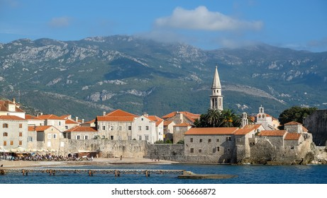 Beautiful scenic view of the old town on sunny day, in Budva, Montenegro. Lots of traditional balkan's red roof houses against the mountain. The old town is surrounded by Adriatic sea