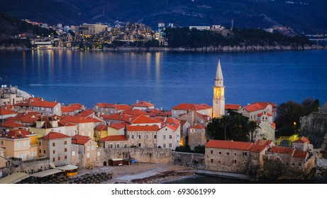 Beautiful scenic view of the old town in the evening dusk, in Budva, Montenegro. Lots of traditional balkan's red roof houses against the mountain. The old town is surrounded by Adriatic sea