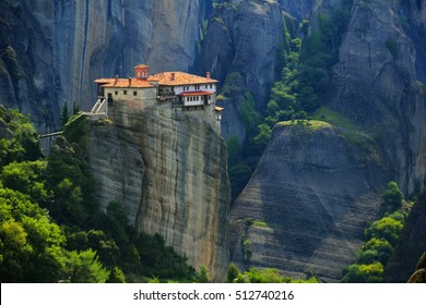 Beautiful scenic view, Orthodox Monastery of Rousanou (St. Barbara),  immense monolithic pillar, green foliage at the background of stone wall in Meteora, Pindos Mountains, Thessaly, Greece, Europe