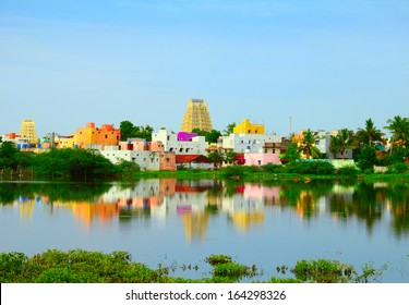 Beautiful scenic view of sacred city Kanchipuram (Kanchi) with colorful traditional houses, gopura of Hindu Temple and bright foliage reflected at calm lake waters, Tamil Nadu, South India