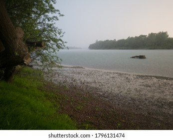 Beautiful scenic view of the Sava River in Bosanski Brod, Bosnia and Herzegovina with fallen tree in front during showers or heavy rain on a gloomy stormy day. Weather forecast for downpour.