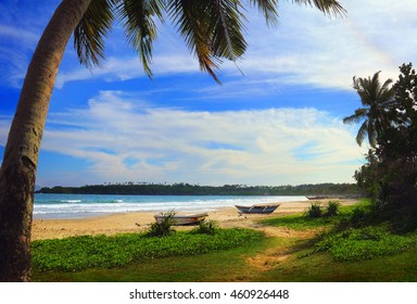 Beautiful scenic view - sea surf, few fishing boats on the sand, palm tree and grass at the background of bright blue sky and Indian Ocean in Tangalla (Tangalle) beach, Sri Lanka island, South Asia