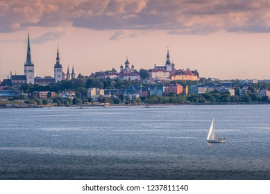 Beautiful scenic view of Tallinn old town from the sea at sunset, sailboat sailing. Panorama view, Tallin skyline