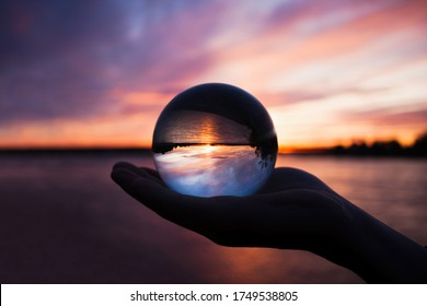 Beautiful scenic view through lens of crystal ball on water horizon at summer sunset. Clouds reflection in sphere. Palm of hand holding globe in outdoor.