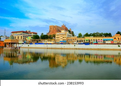 Beautiful scenic view of Trichy (Tiruchirapalli) city with colorful houses, ancient Rock Fort (Rockfort) and Hindu temple reflected at calm pond water, Tamil Nadu, India, South Asia